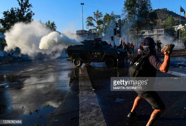 Demonstrators clash with riot police during a protest against Chilean President Sebastian Pinera's government on the constitutional referendum voting...