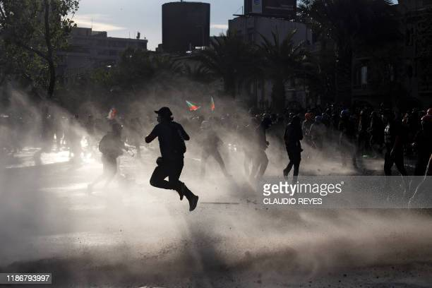 TOPSHOT Demonstrators clash with riot police during a protest against the government of Chilean President Sebastian Pinera in Santiago on December 06...