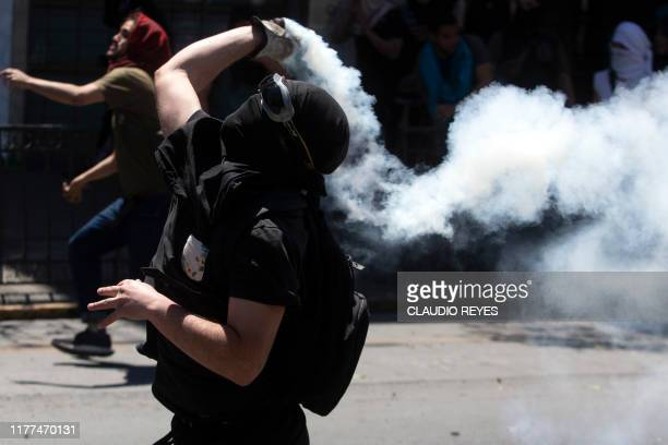 Demonstrators clash with riot police during a protest in Santiago Chile on October 21 2019 Chile ordered an overnight curfew for the third day in a...