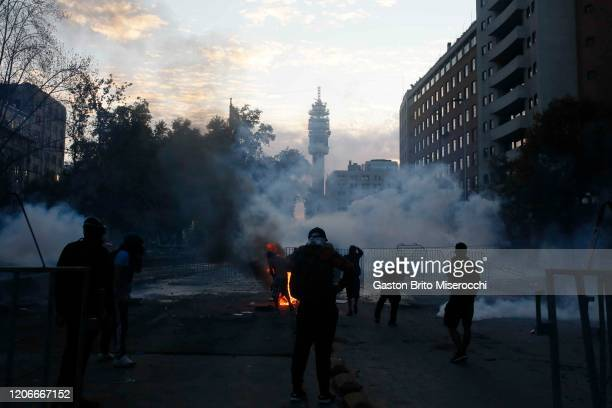 Demonstrators clash with riot police during protests against the government of Sebastián Piñera on its second anniversary on March 11 2020 in...
