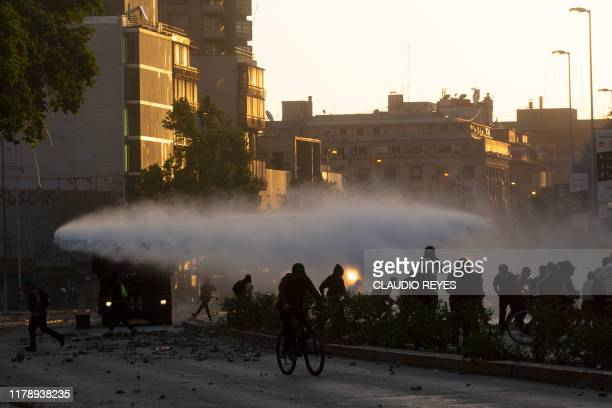Demonstrators clash with riot police during protests against the government economic policies in the surroundings of La Moneda presidential palace in...