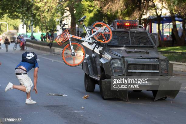 TOPSHOT Demonstrators clash with riot police following a mass faredodging protest in downtown Santiago on October 18 2019 School and university...