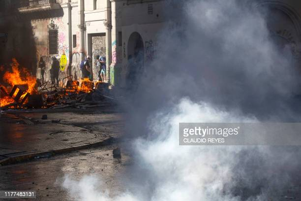 Demonstrators clash with riot police for a fourth straight day as part of protests against a now suspended hike in metro ticket prices in Santiago...