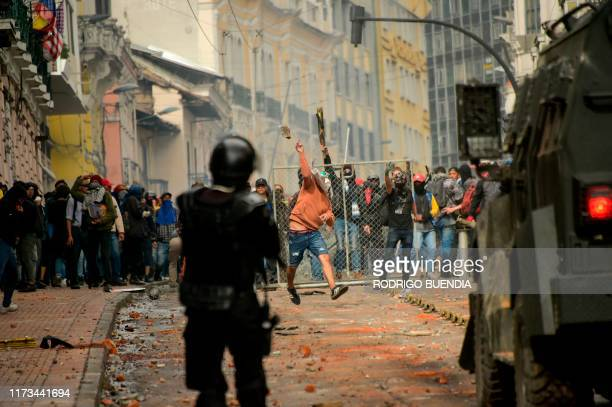 TOPSHOT Demonstrators clash with riot police in downtown Quito during a transport strike against the economic policies of the government of...