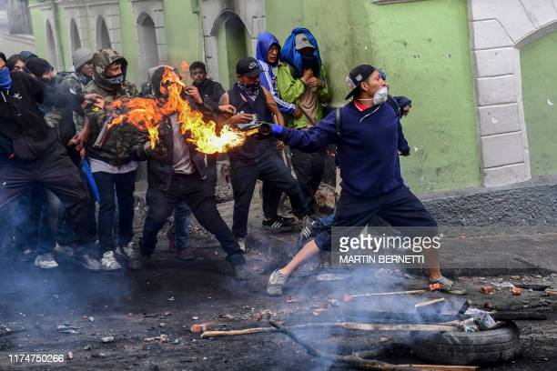 Demonstrators clash with riot police in Quito on October 9, 2019 on the second day of violent protests over a fuel price hike ordered by the...