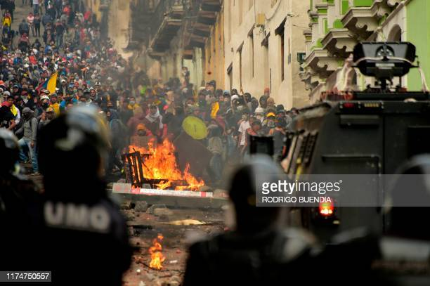 Demonstrators clash with riot police in Quito on October 9 on the second day of violent protests over a fuel price hike ordered by the government to...