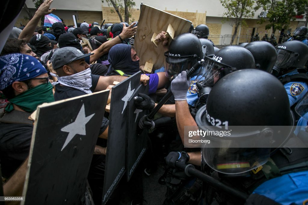 Demonstrators clash with riot police officers during a protest against austerity measures in the Hato Rey neighborhood of San Juan, Puerto Rico, on Tuesday, May 1, 2018. Puerto Rico demonstrators battled police on San Juan's streets as they marched against proposed cuts to retirement benefits and looser labor laws as the bankrupt island seeks to reduce $74 billion of debt. Photographer: Xavier Garcia/Bloomberg via Getty Images