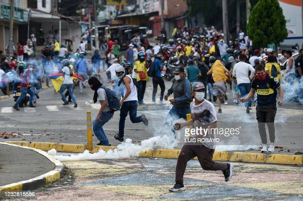 Demonstrators clash with riot police officers during a protest against the government in Cali, Colombia, on May 10, 2021. - Faced with angry street...