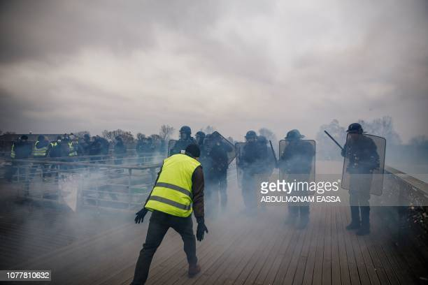 TOPSHOT Demonstrators clash with riot police officers on January 5 2019 in Paris during an antigovernment demonstration called by the yellow vest...