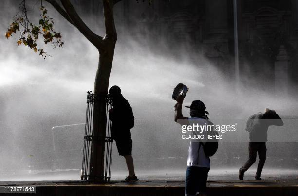 Demonstrators clash with riot police outside La Moneda presidential palace in Santiago on October 28 2019 Chilean President Sebastian Pinera unveiled...