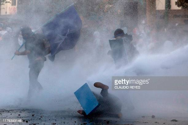 TOPSHOT Demonstrators clash with security forces during the socalled 'Mourning March' in Santiago on November 01 to protest against the death of 23...
