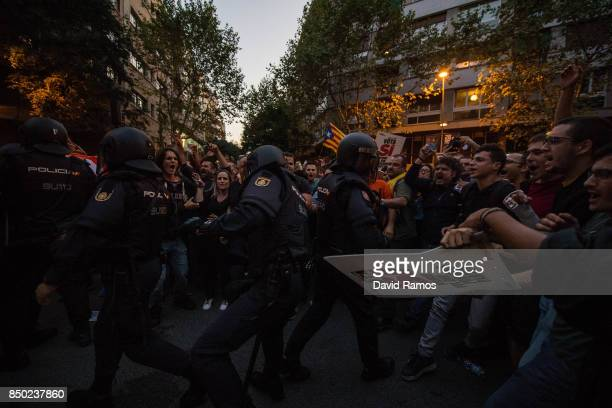 Demonstrators clash with Spanish National Police officers as they leave the road outside the Catalan ProIndependence Lefty party CUP headquarters on...