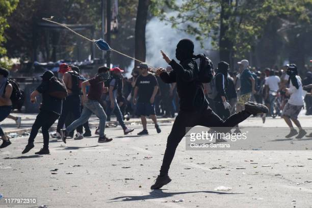 Demonstrators clash with the police during the seventh day of protests against President Sebastian Piñera on October 24 2019 in Santiago Chile...