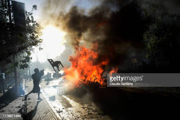 Demonstrators clash with the riot police during a protest against President of Chile Sebastian Piñera after massive protests against his policies at...