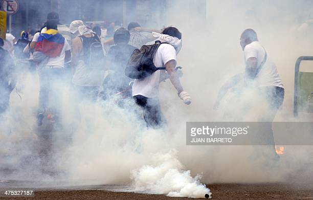 Demonstrators clash with the riot police during an antigovernment protest in eastern Caracas on February 27 2014 Dueling demos of pro and...