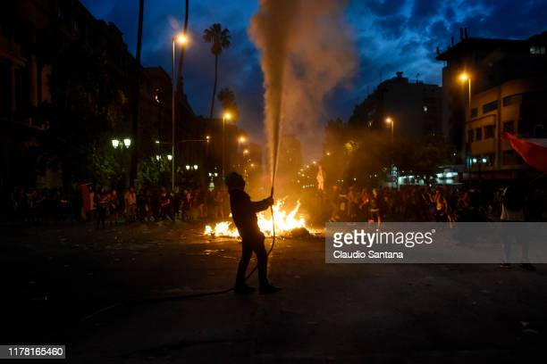 Demonstrators clash with the riot police during the eighth day of protests against President Sebastian Piñera's government on October 25 2019 in...