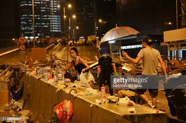TOPSHOT Demonstrators clean a street they occupied in Hong Kong on June 12 the night after a protest against a controversial extradition law proposal...