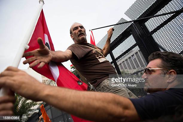 Demonstrators climb on a barrier during a protest against German Chancellor Angela Merkel's visit to Greece for meetings with Greek Prime Minister...