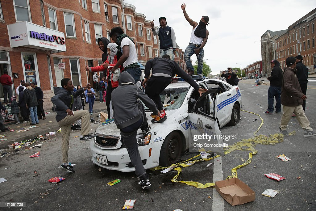 Demonstrators climb on a destroyed Baltimore Police car in the street near the corner of Pennsylvania and North avenues during violent protests following the funeral of Freddie Gray April 27, 2015 in Baltimore, Maryland. Gray, 25, who was arrested for possessing a switch blade knife April 12 outside the Gilmor Homes housing project on Baltimore's west side. According to his attorney, Gray died a week later in the hospital from a severe spinal cord injury he received while in police custody.