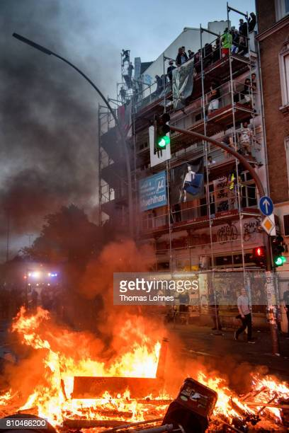 Demonstrators climb scaffolding next to a burning crush barrier during a demonstration against the G20 Summit on July 7 2017 in Hamburg Germany...