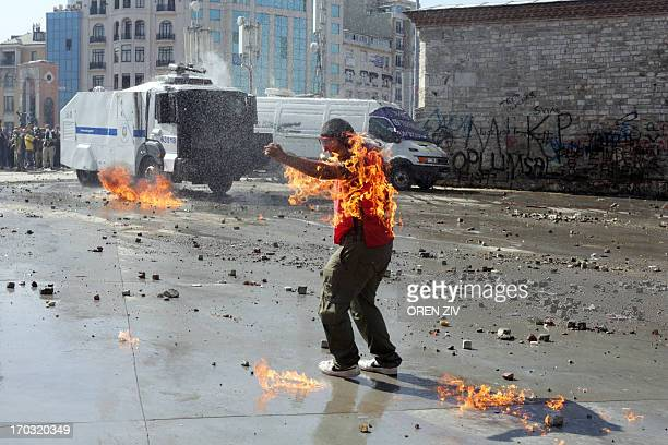 A demonstrator's clothes are set on fire during clashes with riot police in Taksim square on June 11 2013 Riot police stormed Istanbul's protest...
