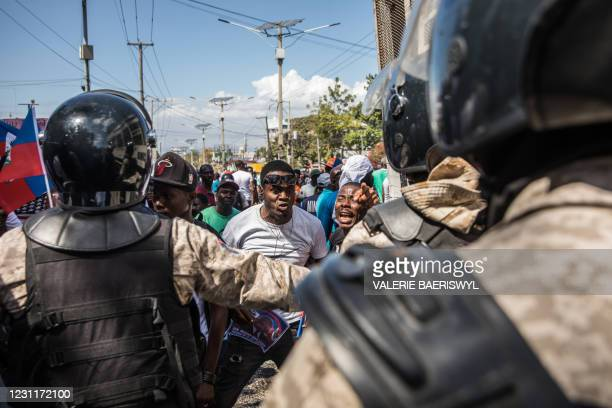 Demonstrators confront police officers as they march in Port-au-Prince on February 14 to protest against the government of President Jovenel Moise. -...