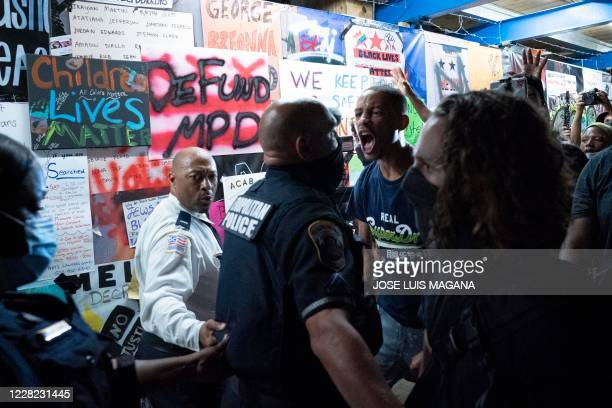 Demonstrators confront police officers during a rally to protest US President Donald Trump's acceptance of the Republican National Convention...