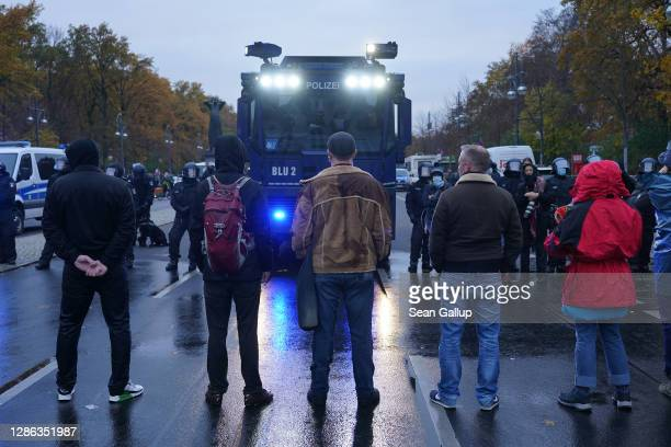 """Demonstrators confront riot police and a water cannon during protests next to the Reichstag against modifications to a law called the """"infection..."""