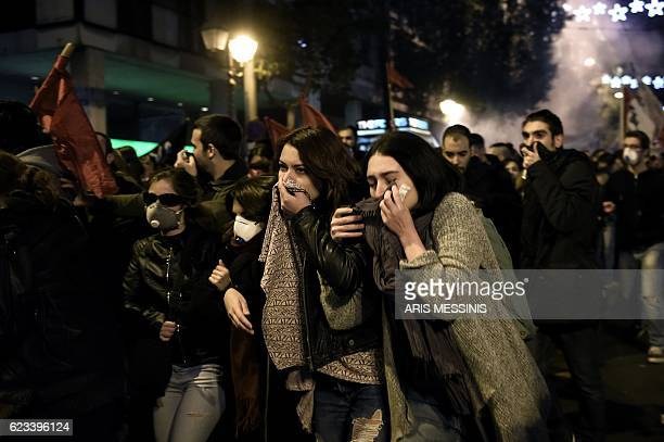 TOPSHOT Demonstrators cover their faces and disperse after tear gas was fired during clashes with Greek riot police during a protest against the...