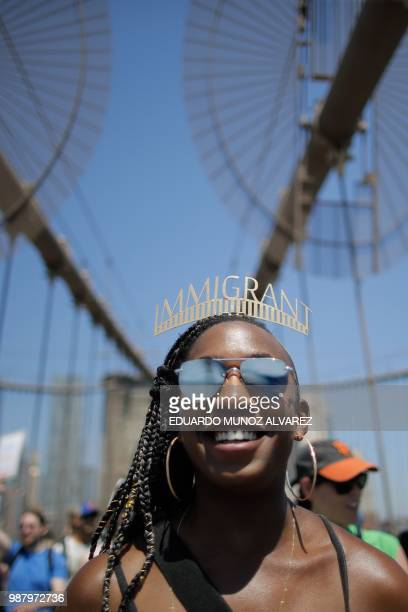 Demonstrators cross the Brooklyn Bridge as they march against the separation of immigrant families on June 30 2018 in New York Demonstrations are...