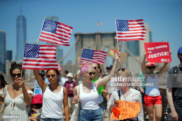 Demonstrators cross the Brooklyn Bridge during a march against the separation of immigrant families on June 30 2018 in New York Demonstrations are...