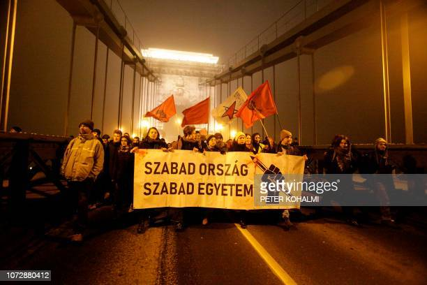 TOPSHOT Demonstrators cross the Chain Bridge with a banner reading 'Free country Free university Peti' during a protest against the dubbed 'slave...