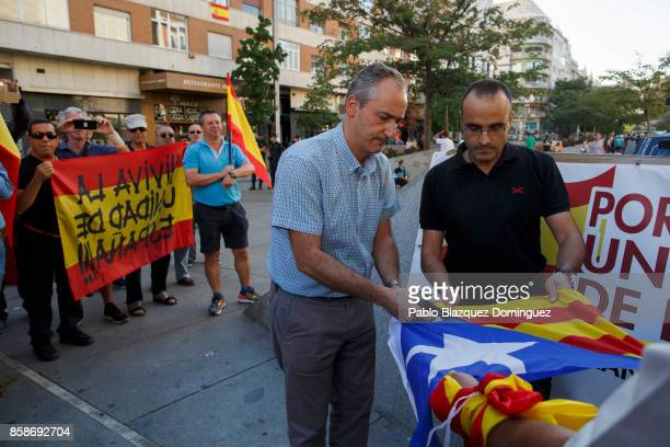 Demonstrators cut off the star from a Catalan ProIndependence flag known as 'Estelada' during a protest against the independence of Catalonia under...
