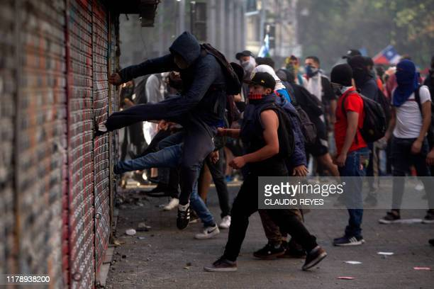 TOPSHOT Demonstrators damage a closed store during a protest against the government's economic policies in Santiago on October 29 2019 Chilean...