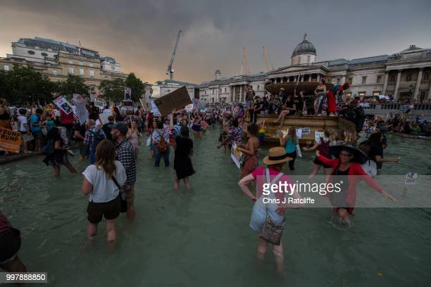Demonstrators dance in fountains after a demonstration against President Trump's visit to the UK in Trafalgar Square on July 13 2018 in London...