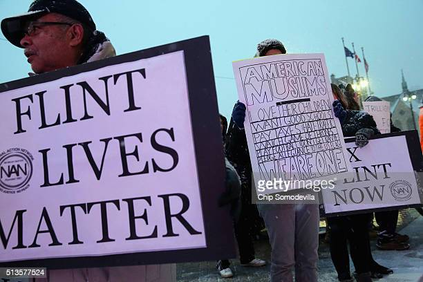 Demonstrators demand action from the Republican presidential candidates about the water crisis in Flint outside the historic Fox Theater before the...