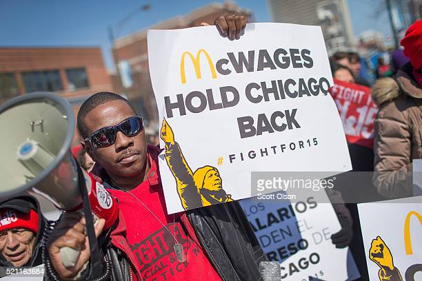 Demonstrators demanding an increase in the minimum wage protest in front of a McDonald's restaurant on April 14 2016 in Chicago Illinois The...