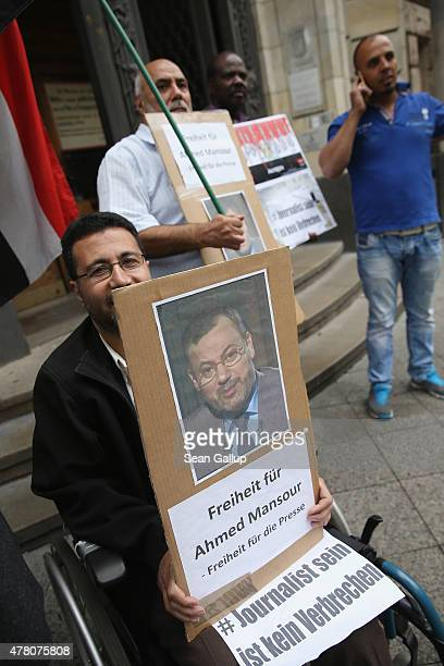 Demonstrators demanding freedom for AlJazeera reporter Ahmed Mansour stand outside the court and prison where Mansour is being held on June 22 2015...