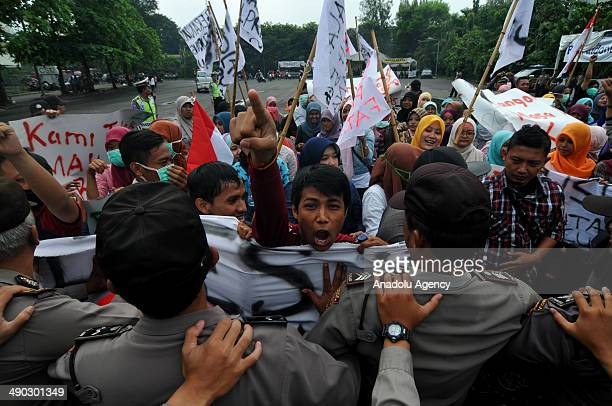 Demonstrators demanding the president reelection clash with Indonesian police during a riot simulation of presidential election on May 14 2014 in...