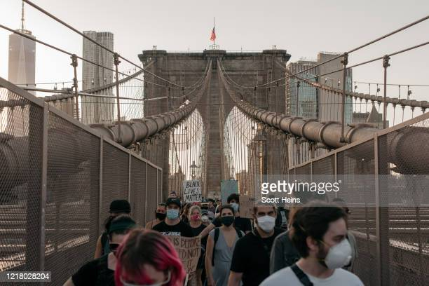 Demonstrators denouncing systemic racism and the police killings of African Americans march over the Brooklyn Bridge on June 6, 2020 in New York...