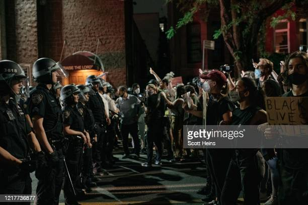 Demonstrators denouncing systemic racism in law enforcement face off with a line of NYPD officers hours after violating a citywide curfew on June 4,...