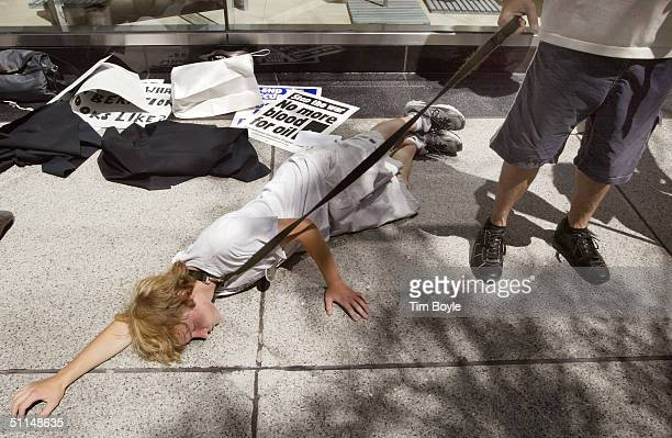 Demonstrators depict an Abu Ghraib prison incident as they protest outside a hotel where US Secretary of Defense Donald Rumsfeld was speaking August...