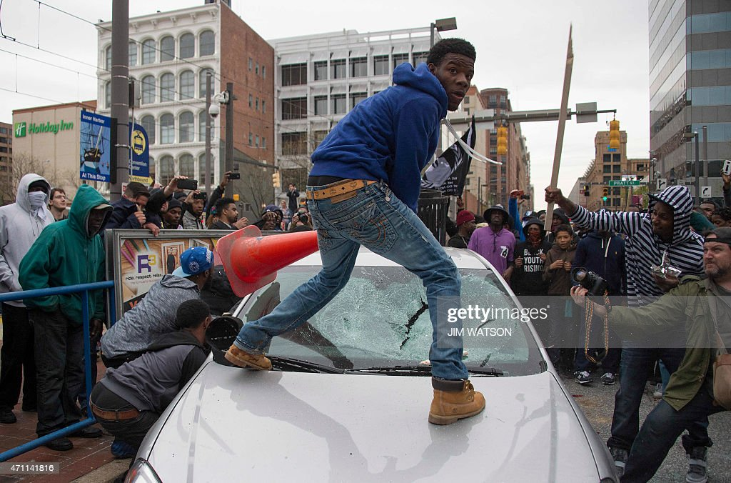 Demonstrators destroy the windshield of a Baltimore Police car as they protest the death Freddie Gray, an African American man who died of spinal cord injuries in police custody, in Baltimore, Maryland, April 25, 2015. Protesters returned to Baltimore's streets Saturday to vent outrage over the death of Gray on April 12.