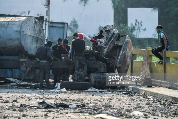 Demonstrators dismantle a truck which was burnt down at the Simon Bolivar international in San Antonio Venezuela as seen from Cucuta Colombia on...