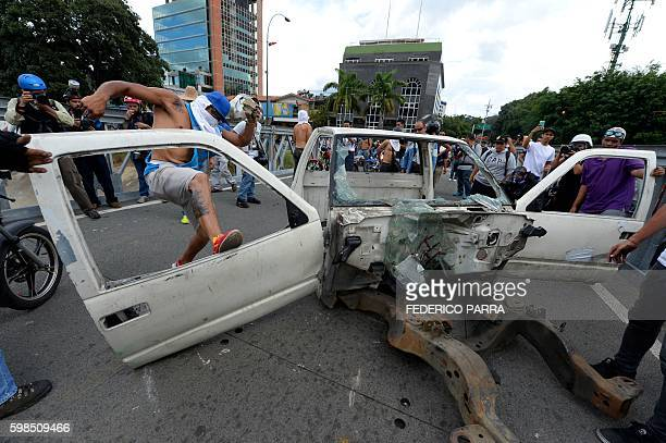Demonstrators dismantle an old car carcass to make a barricade during a march of opposers in Caracas on September 1 2016 Venezuela's opposition and...
