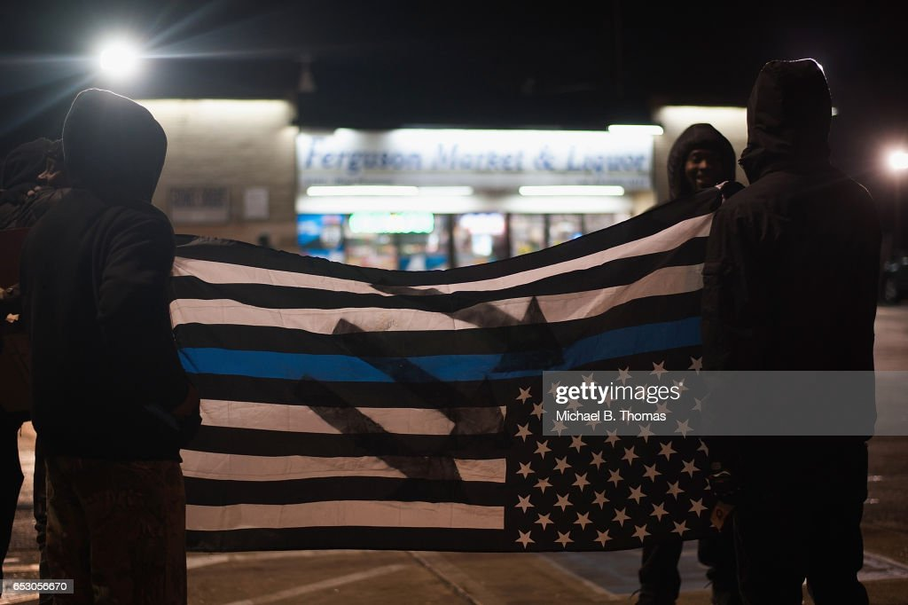 Demonstrators display a distressed American flag that symbolizes support for law enforcement as they protests outside the Ferguson Market and Liquor on March 13, 2017 in Ferguson, Missouri. Tension and protest in Ferguson has arisen in response to video footage of slain 18 year-old Michael Brown in a recent documentary.