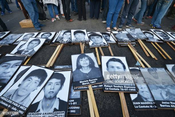TOPSHOT Demonstrators display banners portraying the victims of repression during the ruling of Alberto Fujimori as they march in Lima for the fifth...