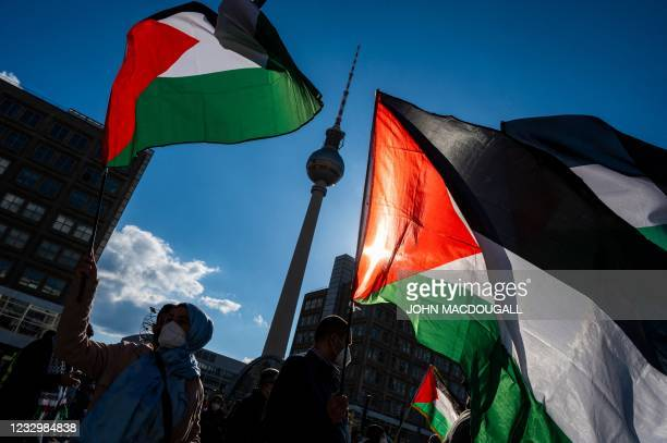 Demonstrators display Palestinian flags during a pro-Palestinian protest at Alexander Platz with the landmark TV Tower in the background in Berlin on...