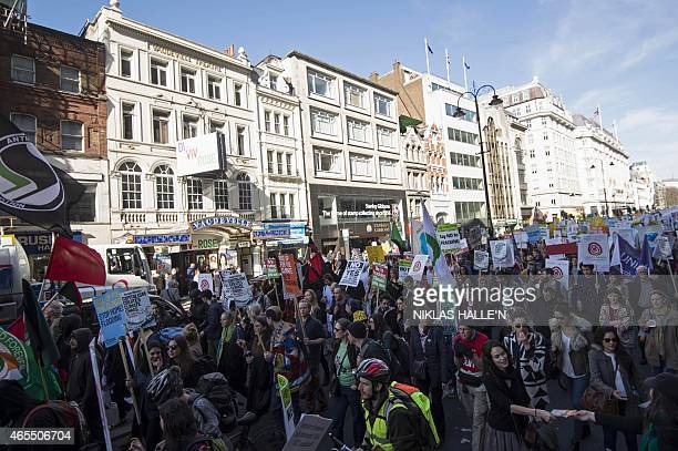 Demonstrators display placards and banners as they attend The People's Climate march in central London on March 7 2015 Around 5000 protesters marched...