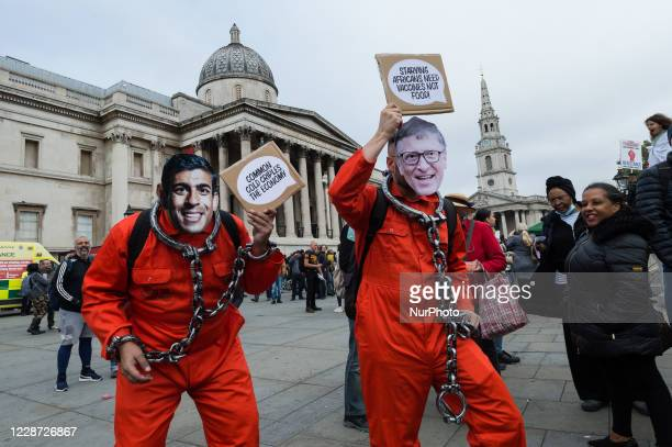 Demonstrators dressed as Chancellor of the Exchequer Rishi Sunak and Bill Gates in prison uniforms take part in Unite for Freedom rally in Trafalgar...